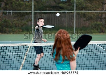 Young kids playing Pickleball on an outdoor court.  - stock photo