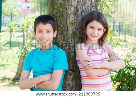 Young kids posing near a tree in the park - stock photo