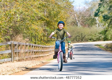 Young kids riding bikes on rural road - stock photo