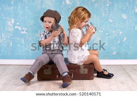 Young kids talking with tin can telephone on grunge background.