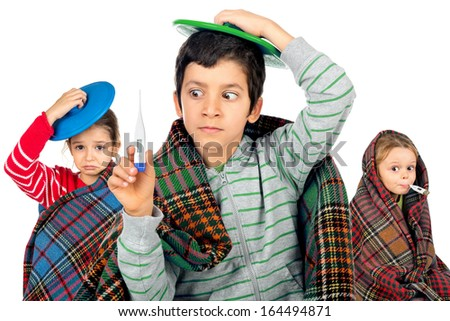 Young kids with a cold wrapped in a blanket with a thermometer - stock photo