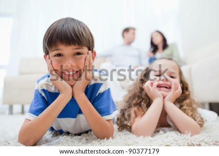 Young kids with lying on the carpet with parents sitting behind them - stock photo