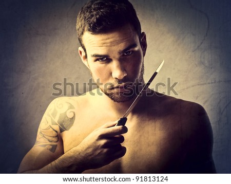 Young killer holding a knife - stock photo