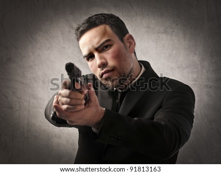 Young killer pointing a gun