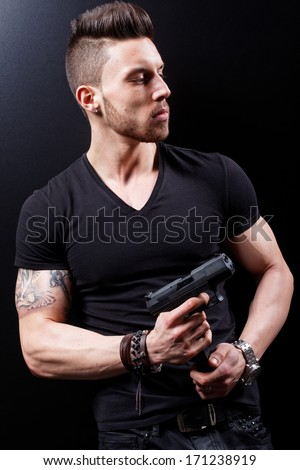 Young killer pointing a gun .Low light. - stock photo