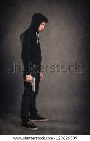 Young killer with gun portrait over dark grunge background. Full body. - stock photo