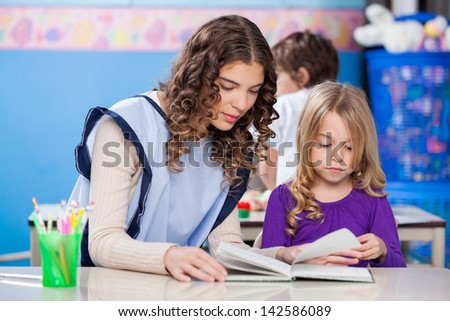 Young kindergarten teacher and little girl reading book in classroom