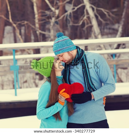 Young kissing couple in love outdoors in the winter with a red heart in hands. valentine's day