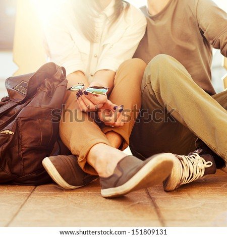 Young kissing happy couple in love sitting on the ground in summer sunny evening - stock photo