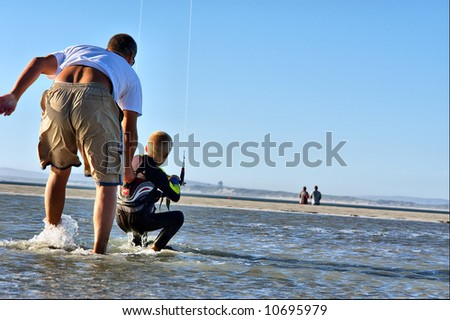 Young kite surfer's training on beach. Shot in Langebaan, Western Cape, South Africa. - stock photo