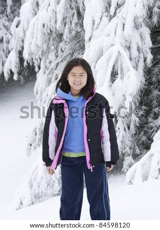 Young Korean girl standing in front of a snow covered tree - stock photo