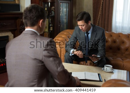 Young Korean or Chinese businessman holding a meeting with your partner. Sit in an expensive beautiful interior, luxury - stock photo