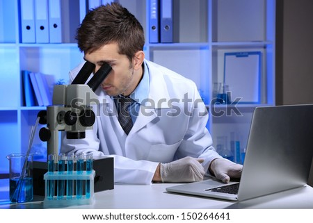 Young laboratory scientist  looking at microscope in lab - stock photo