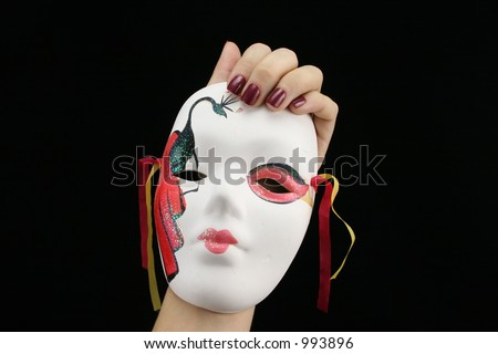 Young ladies hand holding Mardi Gras mask with black background.