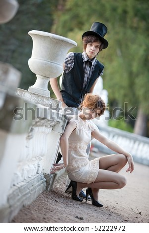Young lady and gentleman at the antique railing. Camera angle view. - stock photo