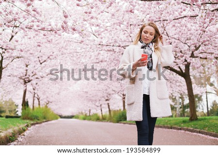 Young lady at spring park listening music from her mobile phone. Relaxed woman taking a walk at spring blossom garden listening music. - stock photo