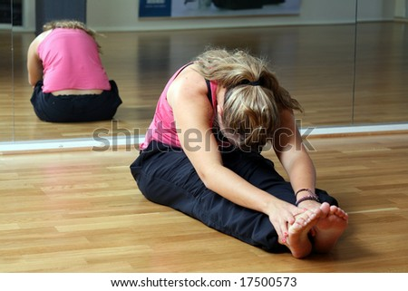 Young lady at the gym in sports position stretching - stock photo