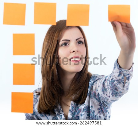 Young lady attaches sticker to the board. Portrait of casually dressed female putting orange paper sticker to the transparent desk. The image made throw transparent glass board. Focus on woman face. - stock photo