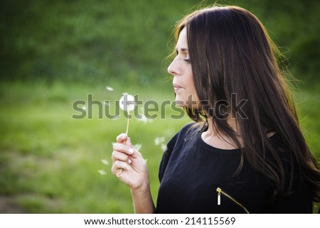 Young lady blowing dandelion flower - stock photo