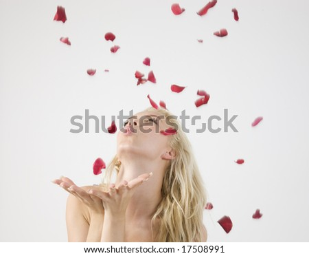 young lady blowing petals on isolated studio picture