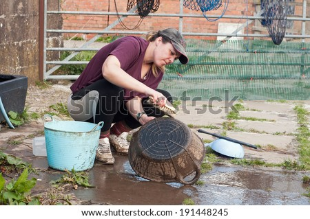 Young lady cleaning her muddy buckets. - stock photo