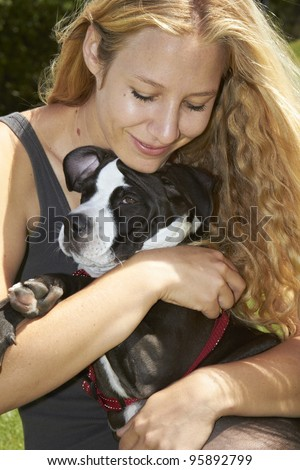 Young lady cuddles her Pit Bull puppy - stock photo