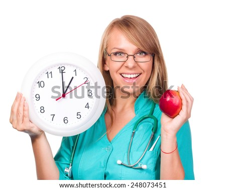 Young lady doctor is holding clock showing one ,over white - stock photo