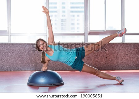 Young lady doing exercises on the bosu ball - stock photo