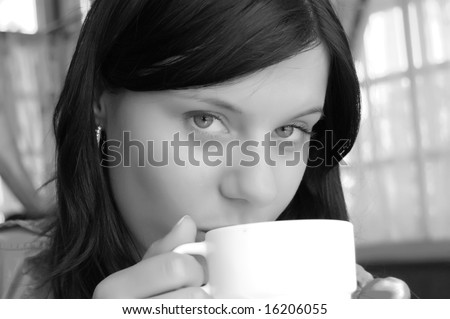Young lady drinking a cup of coffee (black and white photo)