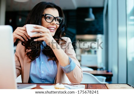 Young lady drinking coffe and looking through a window - stock photo