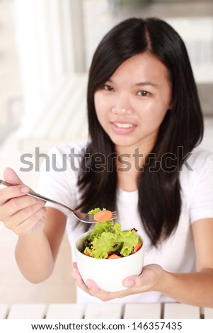 young lady eating vegetable salad at a restaurant
