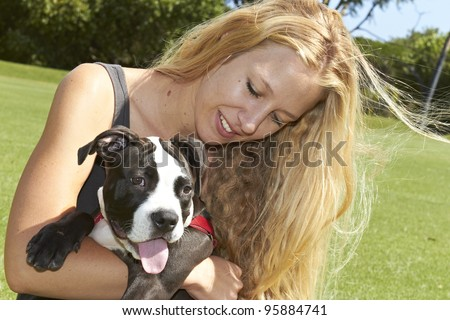 Young lady embracing her panting Pit Bull puppy - stock photo