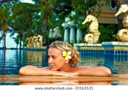 Young lady enjoying spa procedures in the open air pool