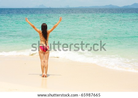 Young lady enjoying sunshine on beach - stock photo