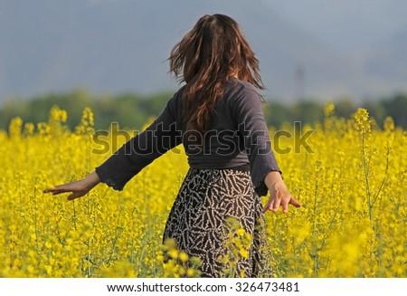 Young lady enjoying touching rape yellow flowers - stock photo