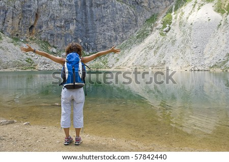 Young lady exploring mountain lake. Dolomites (Lake Boè), Italy. - stock photo
