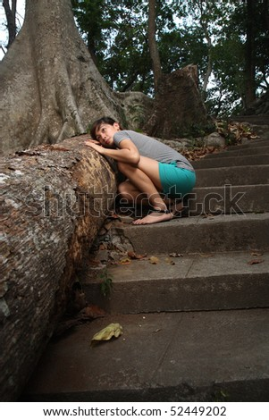 young lady feeling sad over a dead tree
