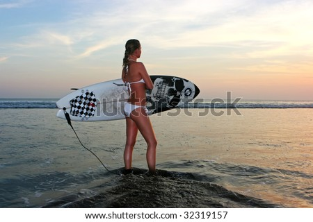 Young lady going to surf at sunset - stock photo