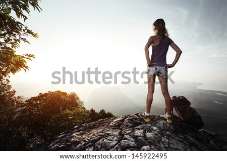 Young lady hiker with backpack enjoying sunrise from top of a mountain - stock photo