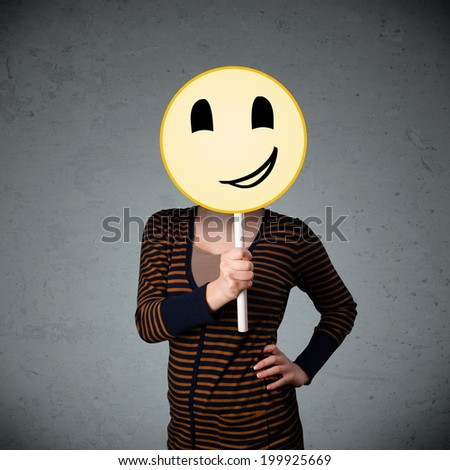 Young lady holding a yellow smiley face emoticon in front of her head - stock photo