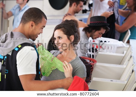 Young lady holding underwear in front of man in laundromat - stock photo