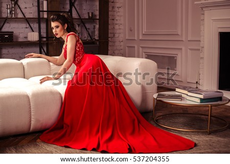 young lady in a gorgeous red evening dress in interior