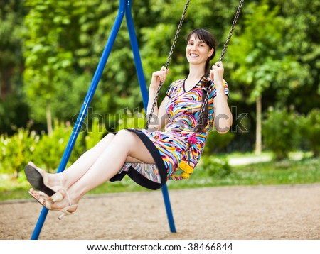 Young lady in a short colorful dress on a swing - shallow DOF - stock photo
