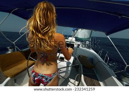 Young lady in bikini steering the yacht - stock photo