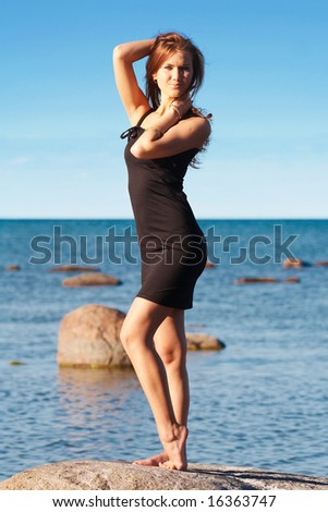 Young lady in black dress near the sea touching her hair