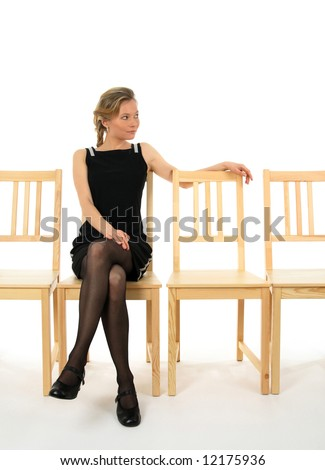 Young lady in black sitting on a chair and waiting for someone. - stock photo