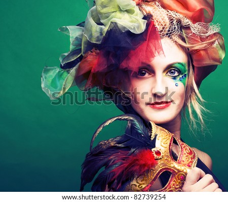Young lady in carnival costume with mask in her hands - stock photo