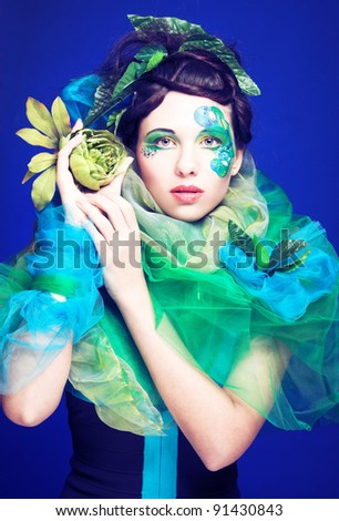 Young lady in creative artistic image and with green flowers