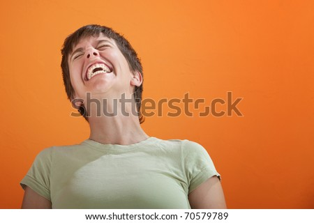 Young lady in green shirt unable to control her laughter