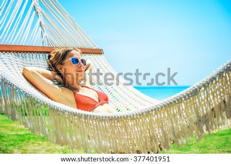 Young lady in hammock on a beach. Vacation concept